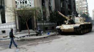 يرجل يقترب من عربة مصفَّحة في شارع وسط القاهرة