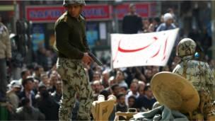 """جندي وسط المتظاهرين ولوحة تحمل كلمة """"ارحل"""""""