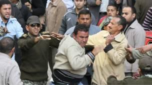 جنود يحاولون حماية شخص ظن المتظاهرون أانه شرطي متخفِّ.