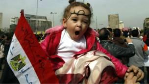 متظاهرة تحمل ابنتها