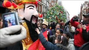 在经济不景气下,民众争相与中国财神合影,希望能够带来好运。