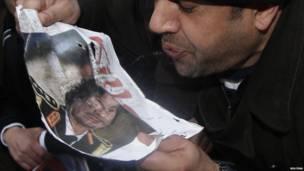 متظاهر ليبي يبصق على صورة للزعيم الليبي معمر القذافي