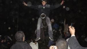 شاب ليبي يتسلق دبابة سيطر عليها المتظاهرون