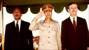 Libyan leader Muammar Gaddafi salutes, beside Egyptian president Anwar Sadat (left) and Syrian President Hafez al-Assad (right) during a military parade in May 1971