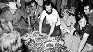 Picture dated July 1973 of Libyan leader Col Muammar Gaddafi (L) joking in Tripoli with a group of British hippies.