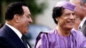 Egyptian President Hosni Mubarak and Libyan leader Muammar Gaddafi laugh at the presidential palace in Cairo, 21 July 2002