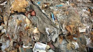 Мальчик спит на горе мусора