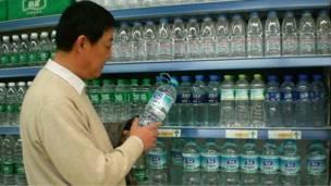 رجل يشترى زجاجة من المياه من متجر في محافظة زيان في الصين
