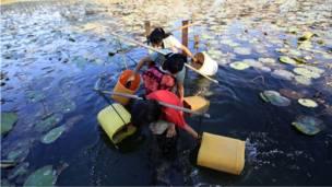 نساء بورميات يجلبن المياه من احدى البحيرات القريبة من قريتهن