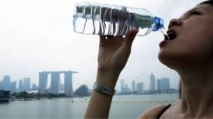 فتاة سنغافورية تشرب زجاجة من المياه أمام خزان مارينا وسط المدينة
