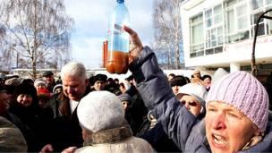 امرأة تعرض عينة من المياه الملوثة التي جلبتها من صنبور منزلها خلال مظاهرة في بلدة بالقرب من موسكو