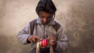 Мужчина делает мяч для игры в крикет