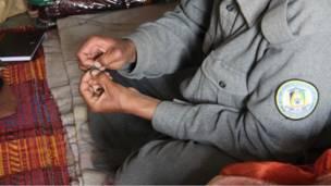 د پولیسو په لیکو کې د نشه یي توکو کارول ډېر شوي دي . یو افغان ګزمه کوونکی سرتېری، چې مخ یې پټ کړی، خپل سګرېټ له چرسو ډکوي .