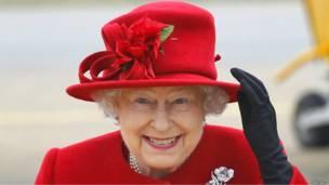 Королева Великобритании придерживает шляпу