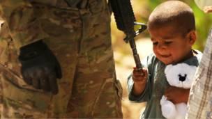 Маленький ребенок в Афганистане трогает оружие американского солдата