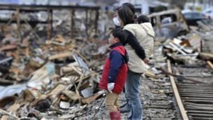 Японская семья перед руинами