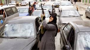Женщина из числа ливийских повстанцев стреляет из автомата
