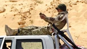 Ливийский повстанец отдыхает на крыше автомобиля