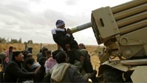 Ливийские повстанцы совместными усилиями заряжают установку залпового огня
