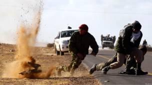 Ливийские повстанцы пытаются укрыться от шрапнели