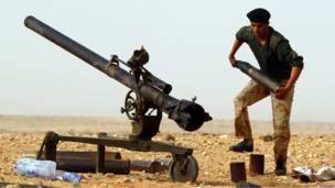 Ливийский повстанец заряжает пушку