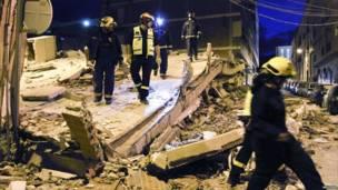 Сотрудники спасательных служб осматривают разрушенное здание