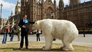 Двойник Камерона стоит рядом с чучелом белого медведя на фоне парламента