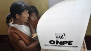 Una mujer vota con su hija