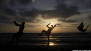 Палестинська молодь витанцьовує на пляжі на заході сонця.
