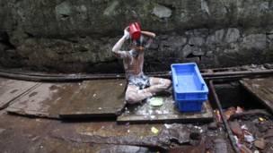 Ребенок принимает ванну в трущобах Мумбаи