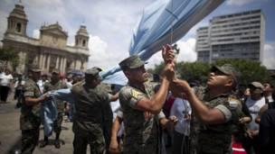 Soldados arreando la bandera de Guatemala