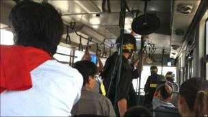 Nhà báo và những người biểu tình bị bắt giữ ngồi trên xe buýt