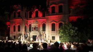 На фоне дома артисты исполняют оперу