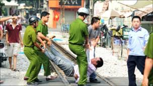 Một người biểu tình chống Trung Quốc bị cảnh sát và an ninh khiêng đi một cách thô bạo. (Hình: AP)