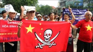 một nhóm người biểu tình cầm lá cờ TQ với hình ảnh cướp biển. (AP)