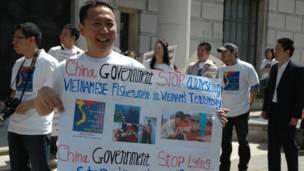 Một Việt Kiều cầm biểu ngữ tại cuộc phản đối.