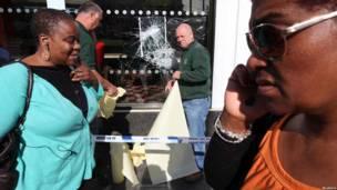 Лондонцы идут мимо ограбленного магазина в Брикстоне