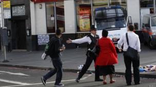 Полицейский заграждает дорогу пешеходам, проходящим мимо бойни в Брикстоне
