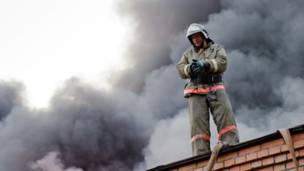 Пожарный стоит на крыше