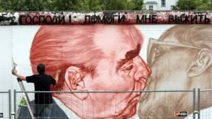 ۲۰۰۹: روسی رسام دمیتري فروبیل پر دېوال د مخکني روسي مشر لیونید بریژنیف عکس کاږي چې د دیموکراتیک المان مشر اریش هونیکر ماچې کوي.