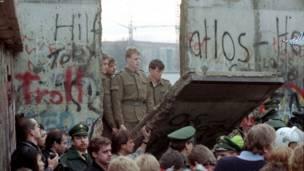 ۱۹۸۹، د نومبر ۱۱مه: د ختيځ المان پوځيان د خپلو هغو هېوادوالو تماشا کوي، چې د ددېوال په ټوټه- ټوټه کولو بوخت دي.