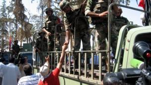 سوريون يصافحون الجيش المنسحب