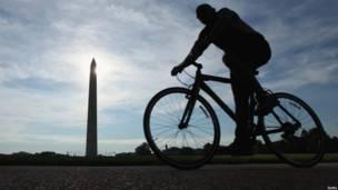 Велосипедист в Вашингтоне на фоне монумента Джорджу Вашингтону