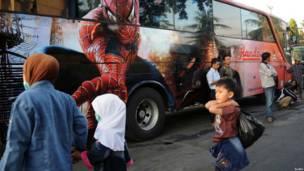 Люди с вещами на автобусной остановке в Индонезии