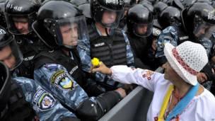 Женщина в Киеве дарит желтый цветок полицейским