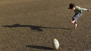 طفل يلعب الرجبي في ملعب بأوكلاند في نيوزيلندا