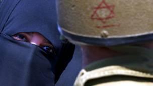 قلندیا، لوېديځه تراډه – یوه فلسطينۍ  ښځه له یوه اسراییلي پوځي سره د فلسطيني ښځو د لاریون پرمهال خبرې کوي.