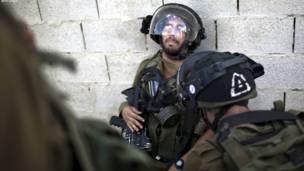 یو اسراییلی پوځي د لوېديځې تراډې په قلندیا کې له فلسطيني لاریون کوونکو سره په اخ و ډب کې.