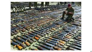 तीन सितंबर 2001 के दिन दक्षिणी मैसिडोनिया में क्रिवोलाक में ग्रीस के सैन्य ठिकाने पर स्थानीय अल्बानियाई लोगों ने हथियार सौंपे. ब्रितानी टास्क फ़ोर्स का एक अधिकारी इस जख़ीरे के बीच से उठाए एक कलाशनिकोव के साथ.