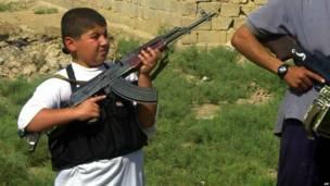 इराक़ में आठ सितंबर 2004 के दिन फ़लूजा में विद्रोहियों की गश्त के दौरान एक बच्चे के हाथों में एके-47 राइफ़ल.